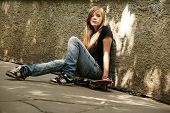 stock photo of runaway  - The girl with skateboard sitting against a wall - JPG