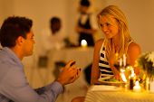 stock photo of proposal  - young man proposing to his girlfriend in a restaurant while having candlelight dinner - JPG