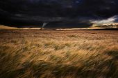 picture of windy weather  - Dark stormy skies over Summer landscape with twister tornado touching down - JPG