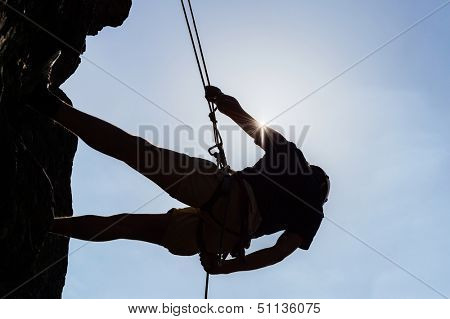 Low angle view of silhouetted man climbing rock against sky