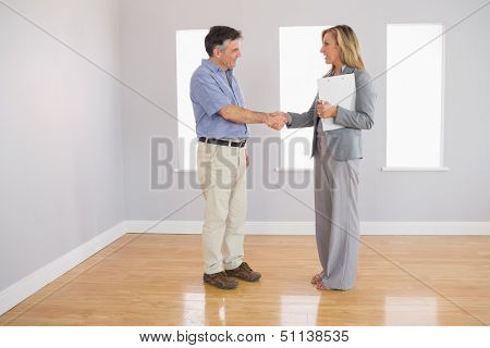 Serious blonde realtor shaking the hand of her mature buyer in an empty room