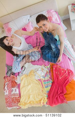 Cute girls making an outfit and looking at camera at sleepover at home in bedroom