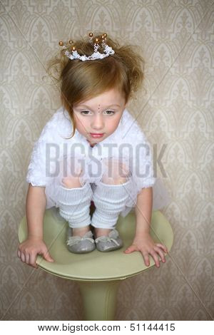A little girl sits on a round chair on his haunches