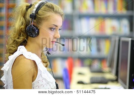 A young woman sitting at a computer wearing headphones in the library hall