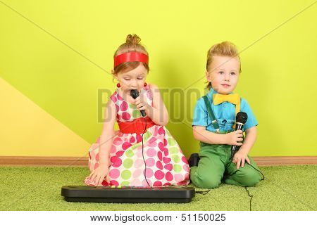 Mods girl and boy with microphones, a girl playing on a toy piano