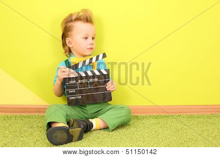 Mod little boy with a clapboard in hands sits at the bright green wall