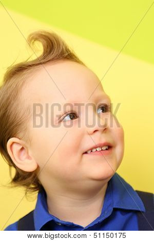 Portrait of a mod little boy in the blue shirt on the background of bright wall