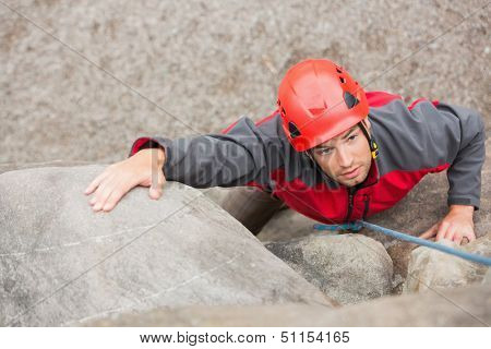 Determined man climbing rock face wearing red helmet