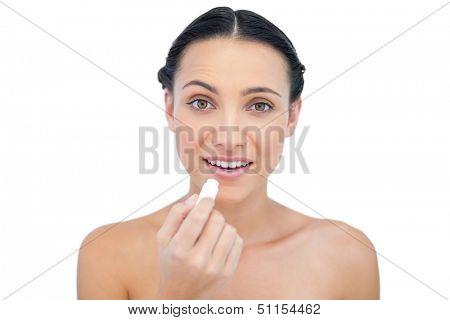 Smiling natural model using lip balm on white background