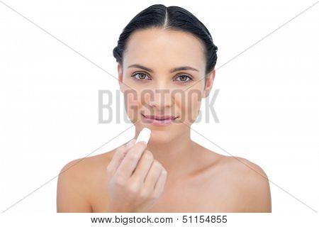 Natural model using lip balm on white background