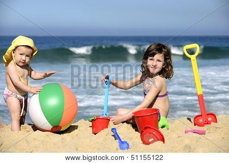 Summer vacation: Kids playing with beach toys in the sand