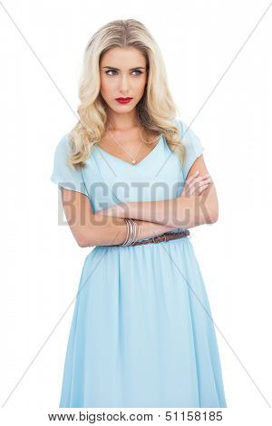 Thoughtful blonde model in blue dress posing crossed arms on white background