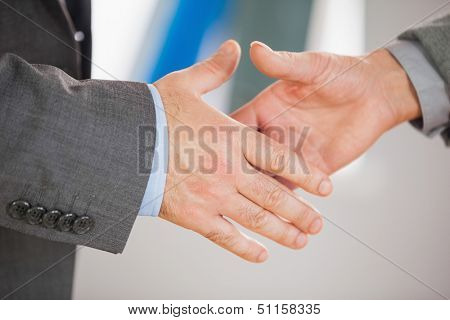 Two business people on the verge of shaking hands in an office