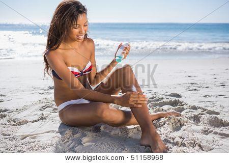 Smiling woman in bikini applying sun cream on her leg while sunbathing on the beach