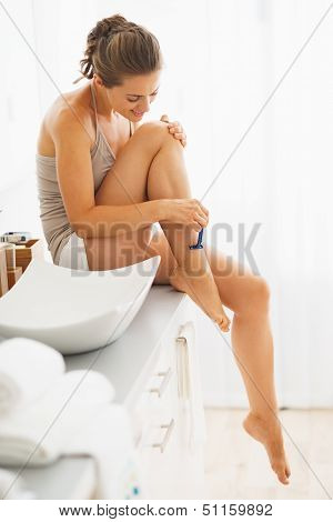 Woman Shaving Legs In Bathroom