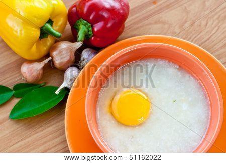 Rice Porridge With Egg In Orange Bowl.