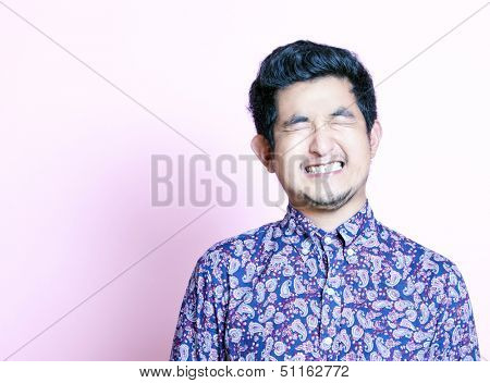 Young Geeky Asian Man in colorful shirt closing both eyes