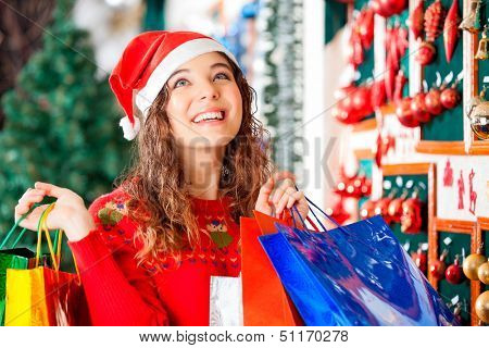 Happy woman in Santa hat looking up while carrying shopping bags at store