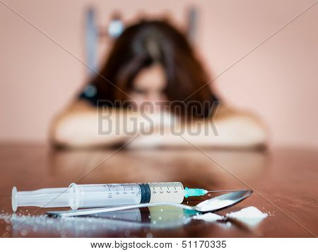 Syringe and drugs with out of focus female drug addict sitting in the backgrouin