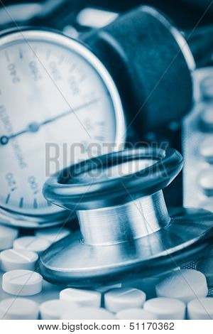 Pills, stethoscope and sphygmomanometer (used to measure blod pressure)  toned in blue shades