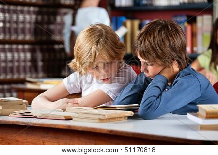 Little boys reading book together while sitting at table in library with classmates in background