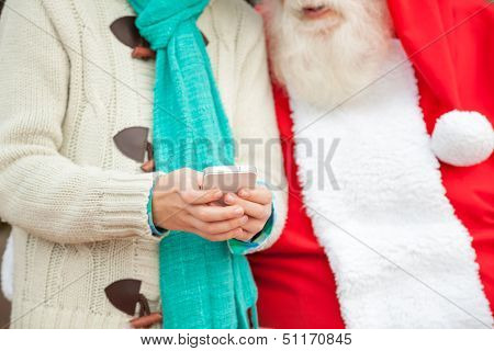 Midsection of Santa Claus with boy using smartphone