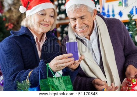 Happy senior couple using mobilephone together at Christmas store