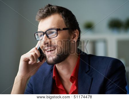 Handsome businessman in smart casual and eyeglasses speaking on the phone