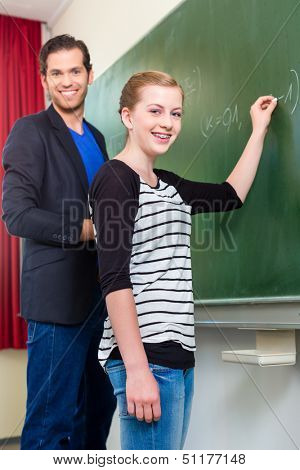Teacher testing while lessons students or girl in school in front of the class at the blackboard or board or chalkboard in math