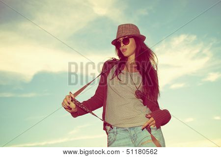 young hipster woman portrait with hat and sunglasses outdoor shot retro colors