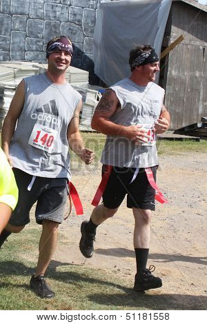 MUSKOGEE, OK - Sept. 14: Runners wearing red life flags overcome obstacles and avoid zombies during the Castle Zombie Run at the Castle of Muskogee in Muskogee, OK on September 14,  2013.