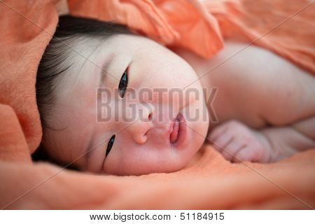Newborn Asian baby girl on bed, 7 days after birth