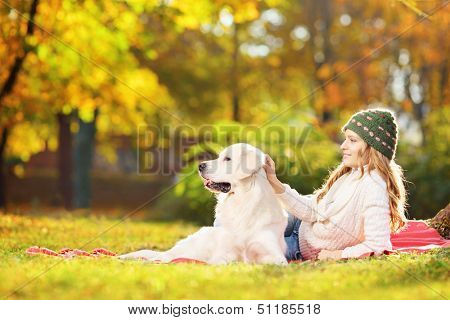Female lying on a green grass with her labrador retriever dog in a park