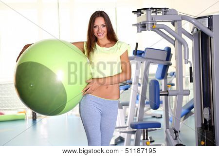 Pretty sporty girl with fit-ball in gum