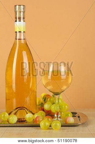 White wine in glass with bottle on salver on beige background