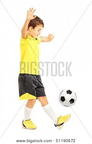 Full length portrait of a boy in sportswear joggling a soccer ball isolated on white background