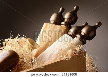 Closeup of ancient scrolls and artifacts in a wooden shipping crate with packing material. Horizontal format with warm tones on a light to dark background.
