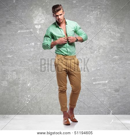 full length photo of a young casual man taking his shirt off while looking into the camera. on gray  vigneta light background