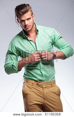 young casual man unbuttoning his shirt and looking at the camera. on light gray background