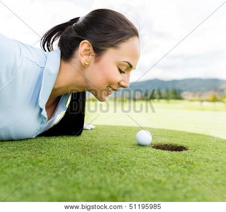 Female golf player blowing the ball into a hole