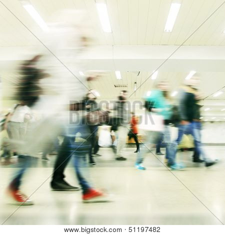 Motion blurred people walking in subway station.