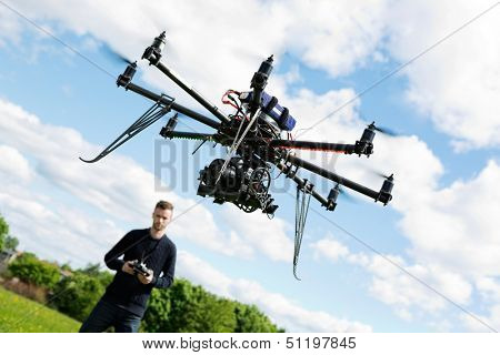 Young technician flying UAV drone with remote control in park