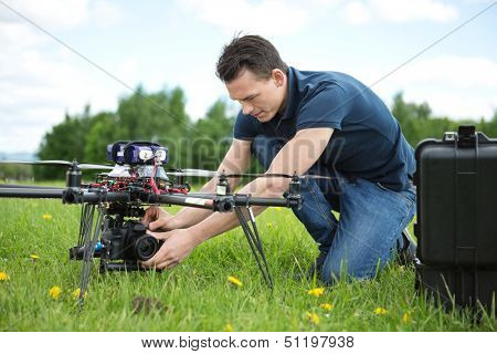 Young technician fixing camera on UAV helicopter in park