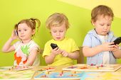 pic of toy phone  - Two boys and a girl with phones in their hands are sitting at a table with toys - JPG