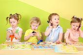 stock photo of toy phone  - Two boys and two girls with phones in their hands are sitting at a table with toys - JPG