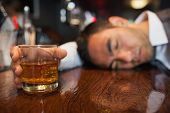 picture of over counter  - Drunk businessman with whiskey in his hand lying on a counter in a classy bar - JPG
