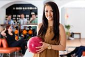 Portrait of beautiful young woman holding bowling ball with people in background at club