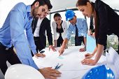 stock photo of team building  - business people group on meeting and presentation  in bright modern office with construction engineer architect and worker looking building model and blueprint planbleprint plans - JPG