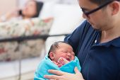 stock photo of bassinet  - Newborn Asian baby girl crying in father - JPG