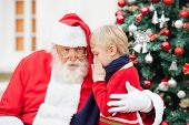 stock photo of nicholas  - Boy whispering in Santa Claus - JPG
